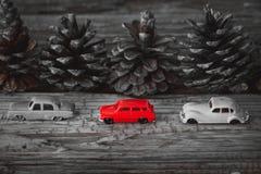 Czerwone samochód zabawki i sosnowe dokrętki na drewnianym stole Fotografia Royalty Free