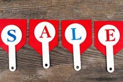 Czerwone sprzedaży etykietki z wpisową sprzedażą na drewnianym tle Zdjęcie Royalty Free