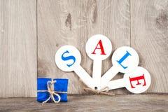 Czerwone sprzedaży etykietki z wpisową sprzedażą na drewnianym tle Fotografia Stock