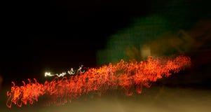 Czerwone squiggly linie przy nocą Obrazy Royalty Free