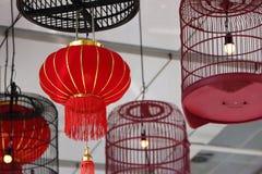 Czerwone tkanin lampy i ptasiej klatki lampy wiesza na suficie Zdjęcia Royalty Free