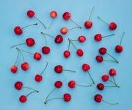 Czerwone wiśnie na błękitnym tle - lata tło Obraz Stock