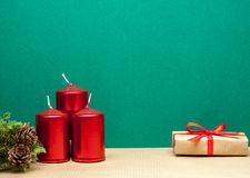 Czerwone świeczki i prezent na zielonym tle Fotografia Stock