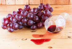 Czerwone wino rozlewający i winogrona Obrazy Royalty Free