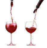 Czerwone wino w szklanym dolewaniu od butelki i robi pluśnięciu, aptekarka na butelce, czerwone wino strumień Obraz Royalty Free