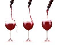 Czerwone wino w szklanym dolewaniu od butelki i robi pluśnięciu, aptekarka na butelce, czerwone wino strumień Fotografia Stock