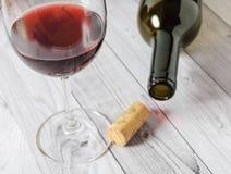 Czerwone wino w szkle i butelce na lekkim drewnianym stole Fotografia Royalty Free