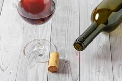 Czerwone wino w szkle i butelce na lekkim drewnianym stole Zdjęcie Stock