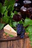 Czerwone wino w szkle otaczającym zakąskami: Maasdam ser, orzechy włoscy i wiązka Isabella winogrona, obraz stock
