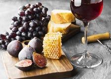 Czerwone wino z figą, ciemni winogrona, miód, chleb na ciemnym backgroun zdjęcia royalty free