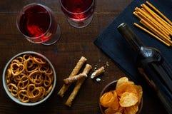 Czerwone wino z pikantnym przyjęciem przekąsza na nieociosanym ciemnym drewnianym backgroun zdjęcie stock