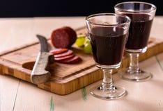 Czerwone wino z salami i winogronami na starym drewno stole i niektóre winogronie Obrazy Stock