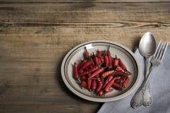 Czerwonego chili pieprz na rocznika talerzu, antykwarskiej srebnej łyżce i rozwidleniu, wysuszeni chillies na drewnianym tle Odgó fotografia stock