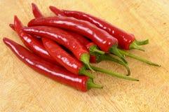 Czerwonego chili pieprze na ciapanie deski zbliżeniu Zdjęcia Stock