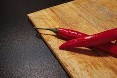 Czerwonego chili pieprze na drewnianej tnącej desce Fotografia Stock