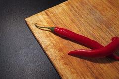Czerwonego chili pieprze na drewnianej tnącej desce Obraz Royalty Free