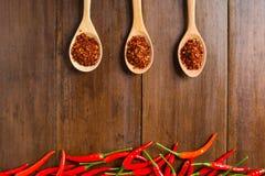 Czerwonego chili pieprze na drewnianym tle Zdjęcia Stock