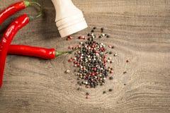 Czerwonego chili pieprzu pieprzowy młyn na drewnianym stole Zdjęcie Royalty Free