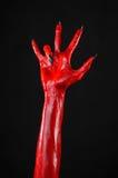Czerwonego diabła ręki z czerń gwoździami, czerwone ręki szatan, Halloweenowy temat na czarnym tle, odizolowywającym Fotografia Stock