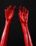 Czerwonego diabła ręki z czerń gwoździami, czerwone ręki szatan, Halloweenowy temat na czarnym tle, odizolowywającym Zdjęcia Stock
