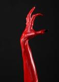 Czerwonego diabła ręki z czerń gwoździami, czerwone ręki szatan, Halloweenowy temat na czarnym tle, odizolowywającym Obraz Royalty Free