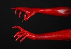 Czerwonego diabła ręki z czerń gwoździami, czerwone ręki szatan, Halloweenowy temat na czarnym tle, odizolowywającym Obrazy Stock