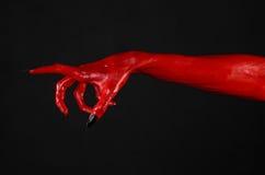 Czerwonego diabła ręki z czerń gwoździami, czerwone ręki szatan, Halloweenowy temat na czarnym tle, odizolowywającym Zdjęcia Royalty Free