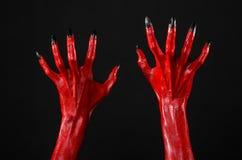 Czerwonego diabła ręki z czerń gwoździami, czerwone ręki szatan, Halloweenowy temat na czarnym tle, odizolowywającym Zdjęcie Stock