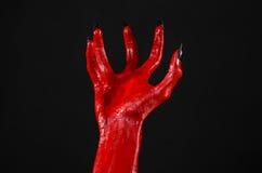 Czerwonego diabła ręki z czerń gwoździami, czerwone ręki szatan, Halloweenowy temat na czarnym tle, odizolowywającym Obraz Stock