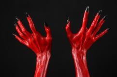Czerwonego diabła ręki z czerń gwoździami, czerwone ręki szatan, Halloweenowy temat na czarnym tle, odizolowywającym Obrazy Royalty Free