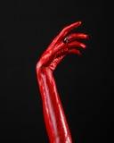 Czerwonego diabła ręki z czerń gwoździami, czerwone ręki szatan, Halloweenowy temat na czarnym tle, odizolowywającym Fotografia Royalty Free
