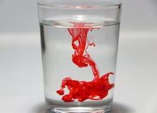 Czerwonego koloru kropla na wodzie w szkle z białym tłem obraz stock