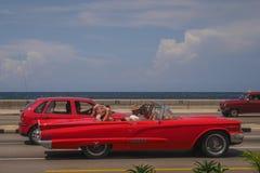 Czerwonego starego rocznika amerykańscy samochody w Hawańskich ulicach obok oceanu Zdjęcia Royalty Free