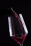 Czerwonego wina dolewanie w wineglass od butelki na czarnym tle Wino listy projekta menu z copyspace Obrazy Royalty Free
