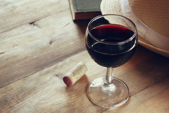 Czerwonego wina szkło i stara książka na drewnianym stole przy zmierzchem pękamy rocznik filtrującego wizerunek Obrazy Stock