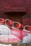 Czerwonej cegły drzwi w ścianie z graffiti obraz royalty free