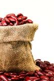 Czerwonej fasoli lub czerwień cynaderki fasola w konopie worku odizolowywającym na białym backg zdjęcia stock
