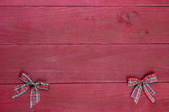 Czerwonej szkockiej kraty Bożenarodzeniowi łęki graniczą na antykwarskim czerwonym drewnianym tle Zdjęcie Royalty Free