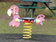 Czerwonej wiosny jeździec przy dziecka boiskiem obraz royalty free