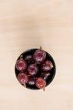 Czerwoni agresty w pucharze na drewnianym stole Obrazy Stock