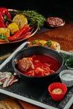Czerwoni barszcze robić beetrot, warzywa i mięso z kwaśną śmietanką w czarnym talerzu, na miedzianym tle fotografia stock