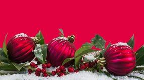 Czerwoni boże narodzenia graniczą tło z baubles w śniegu obrazy stock