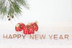 Czerwoni Bożenarodzeniowi baubles i Szczęśliwi nowy rok życzenia Zdjęcie Stock