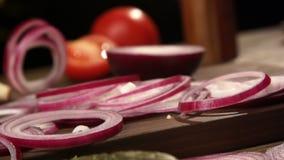Czerwoni cebulkowi pierścionki spadają na tnącej deski slowmo zbiory