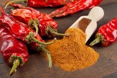 Czerwoni chili pieprze i stos zmielony chłodny zdjęcia royalty free