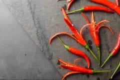 Czerwoni chillies na skale i czerni skale Fotografia Stock
