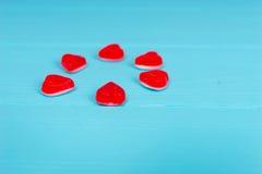 Czerwoni cukierki w formie serca na drewnianym turkusu stole Zdjęcie Royalty Free