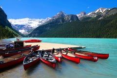 Czerwoni czółna w błękitnym nawadniają Jeziorny Louise, Banff, Kanada zdjęcie royalty free