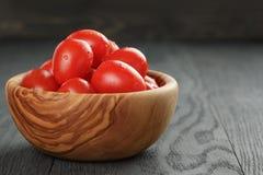 Czerwoni czereśniowi śliwkowi pomidory w oliwnym pucharze na drewnie Zdjęcie Stock