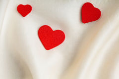 Czerwoni drewniani dekoracyjni serca na białym jedwabniczym tle. Obraz Royalty Free